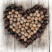 Chestnuts and acorns forming a heart on a wooden background — Stock Photo