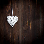 White wicker heart on wooden background — Stockfoto