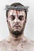 Bleeding man with crown of barbed wire — Stock Photo