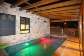 Villa with an illuminated pool at night — Stock Photo