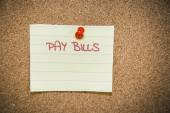 Pay bills note on a bulletin board — Stock Photo