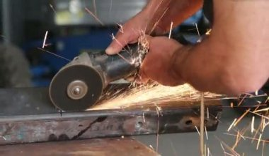 Welder using electric grinder — Stock Video