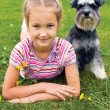 Girl and her dog lying on the grass in the park on a summer day — Stock Photo #51909491