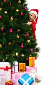 Child in a christmassy red dress peeking out from behind the Christmas tree — Foto Stock
