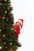Child in a christmas red dress peeking out from behind the Chris — Stock Photo