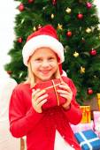 Child in a christmassy red dress peeking out from behind the Christmas tree — Stock Photo