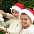 Mother and daughter decorating the Christmas tree and lighting — Stok fotoğraf #55505963