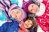 Children lie on the snow in winter and look upwards — Zdjęcie stockowe