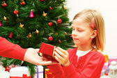 Beautiful little girl receives a Christmas gift — Stock Photo
