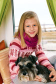 Cute girl sitting on a window sill with his dog — Stock Photo