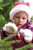 Little girl decorates a Christmas tree on the street — Стоковое фото