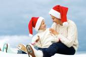Happy family sitting in ice skates and christmas hats — Stock Photo