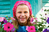 Portrait of a young laughing girl among the flowers — Stock Photo