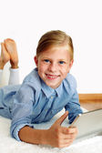 Enthusiastic child lies on the floor and enjoys tablet — Stock Photo