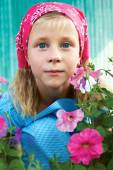 Portrait of a surprised little girl sitting in the garden on a background of pink flowers — Stock Photo