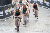 Triathletes in heavy rain with Joao Silva in front on the wet co — Stock Photo