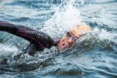 Closeup of a triathlete swimming in the cold water at the Womans — Foto de Stock