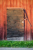 Old weathered black barn door with locks and shingles — Stock Photo