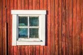 Square white window in old red wooden barn wall — Stock Photo