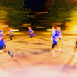 Runners in motion blur and colorful light trails on the streets — Stock Photo #81286868