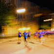 Runners in motion blur and colorful light trails on the streets — Stock Photo #81286874