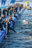 Triathletes jumps into the water for the start in early morning — Stock Photo