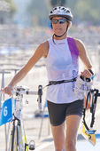 Closeup of female triathlete running with bike and shoes in the — Stock fotografie