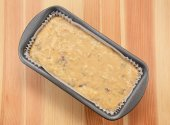 Raw banana loaf batter in a lined tin  — Stock Photo