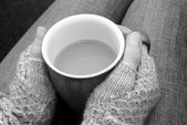 A woman in a cosy jumper holds a cup of tea or coffee on her lap — Stock Photo