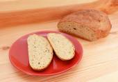 Two slices of bread on a red plate, with a loaf of bread — Stock Photo