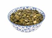 Pumpkin seeds in a blue and white china bowl — Стоковое фото