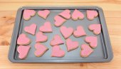 Array of heart-shaped cookies with pink frosting — Stock Photo