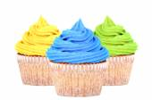 Three cupcakes with yellow, blue and green icing — Stock Photo