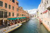 Typical Venetian canal on a sunny day, including restaurants,tourists, hotels, and a small bridge over the canal. — Stock Photo