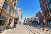 Helsinki, Finland - June 24: People walking on a sunny day, in a typical street at the centre of Helsinki on June, 24 2013. There are some famous shops and stores in this street. — Stock Photo
