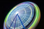Beautiful Long exposure picture of a ferris wheel rotating, vivid colors. — Stock Photo