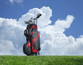 Golf clubs on grass with blue sky and clouds — Stock Photo