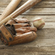 Old baseball, mitt and wooden bats on a rough wood surface — Stock Photo #54709797