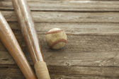 Old baseball and bats on rough wood surface — Stock Photo