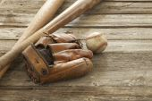 Old baseball, mitt and wooden bats on a rough wood surface — Stock Photo