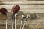 Old golf clubs on rough wood surface — Stock Photo