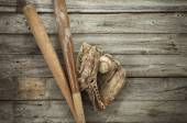 Old baseball with mitt and bats on rough wood — Stock Photo