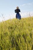 Defocused Amish woman walking in a field — Stock Photo