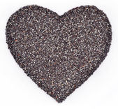 Poppy seeds in the form of heart on a white — Stock Photo