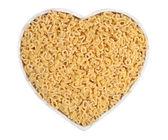 Macarrão de alfabeto em placa em forma de coração em um branco — Fotografia Stock