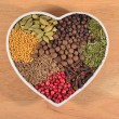 Different dry spices in plate in form of heart — Stock Photo #62685963