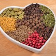 Different dry spices in plate in form of heart — Stock Photo #62685975