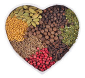 Different dry spices in plate in the form of heart on a white  — Stock Photo