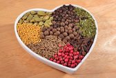 Different dry spices in plate in form of heart  — Stock Photo
