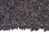 Heap of  black sunflower seeds on a white — Stock Photo